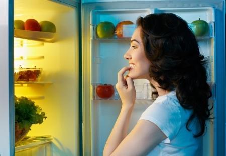 אישה רעבה עומדת מול מקרר פתוח, אחרי התכנית של האחרים גיל כבר לא תפחדו מהתקפים של קרייבינג למתוק