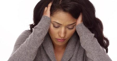 אישה סובלת מכאב ראש או מיגרנה, תסמינים של מחסור במגנזיום עלולים להתבטא במיגרנות