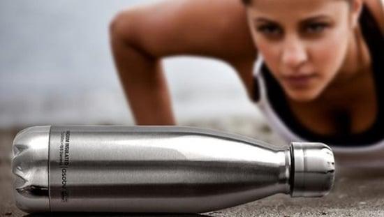 אישה מתאמנת ומסתכלת על בקבוק תרמי של אסובו