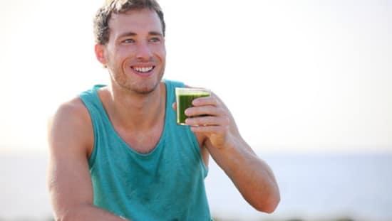בחור ספורטיבי שותה שייק ירוק, שמומלץ להכין עם בלנדר ואקום