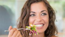 אישה צעירה ויפה אוכלת סלט, שהוא לךק הכרחי מתזונה בריאה