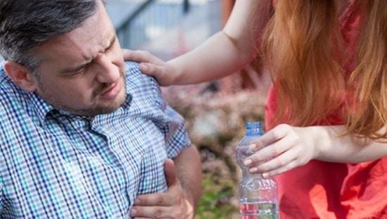 אישה מגישה מים לאדם עם צרבת