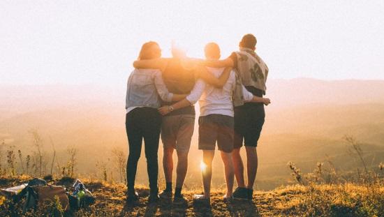 ארבעה אנשים מתחבקים על רק שקיעה