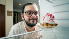 איש מצחיק מסתכל על עוגה במקרר, מצב מוכר של אכילה רגשית