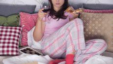 אישה בפיג'מה, יושבת על הספה אוכלת פיצה ושותה יין